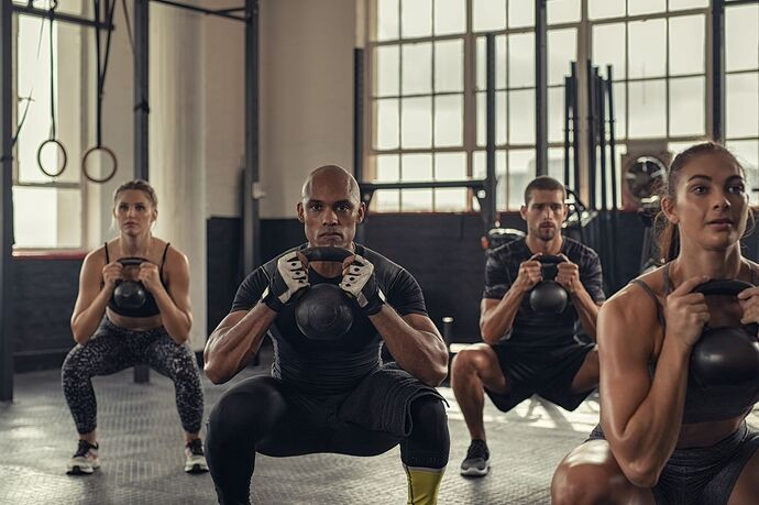 fitness-people-squatting-with-kettlebell-royalty-free-image-1595432236
