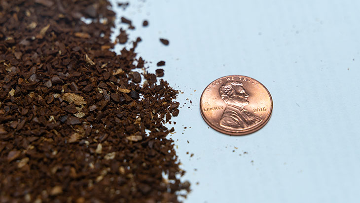 medium course coffee grind with a penny for scale