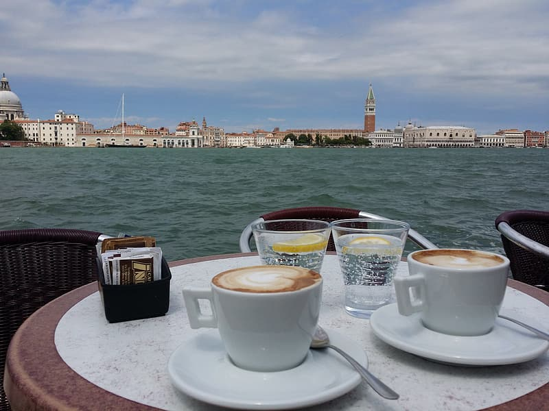 two-ceramic-coffee-cups-on-table-near-body-of-water